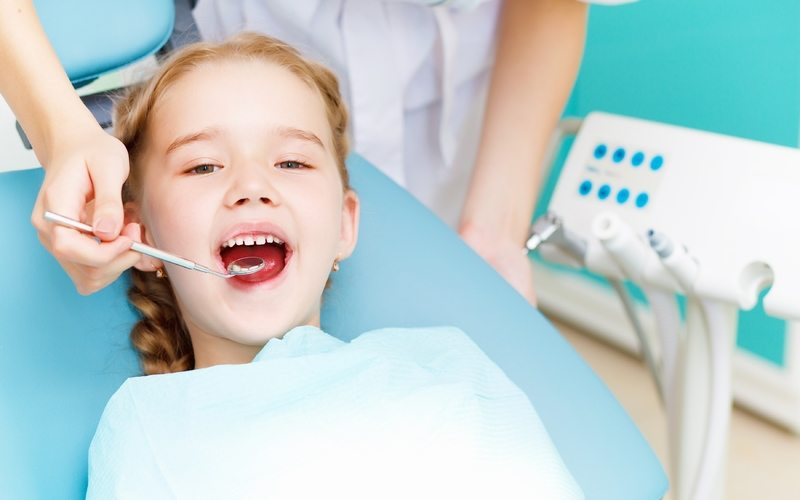 Small girl sits in a dentist chair and says aah for the doctor