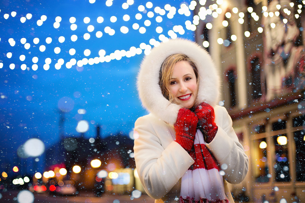 A woman shows off her holiday smile as snow falls around her