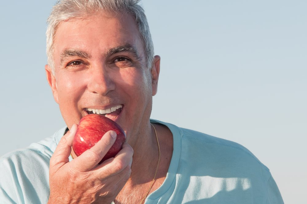 Man with dental implants bites into an apple